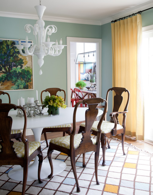 Dining room in a Los Angeles home with light green walls, yellow curtains, a white glass chandelier, and a white table surrounded by high back wood chairs