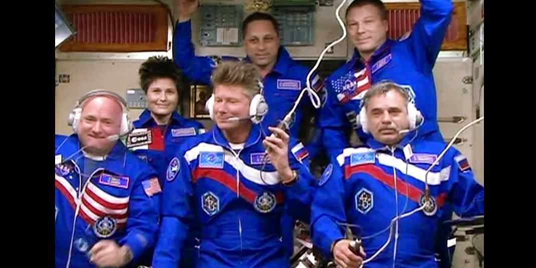 Scott Kelly, Mikhail Kornienko and Gennady Padalka joined their Expedition 43 crewmates Terry Virts, Anton Shkaplerov and Samantha Cristoforetti in the Zvezda service module for a crew greeting ceremony. Credit: NASA TV