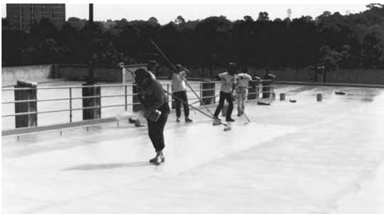 Deck-coating application. Note the pushing of squeegees in the background, back-rolling of coating and spreading of the aggregate by hand in the foreground. All crew members are wearing golf shoes.