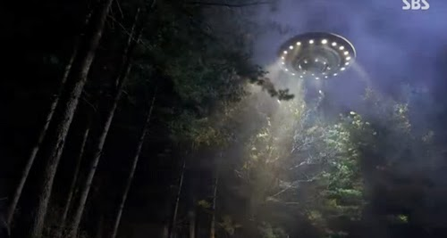 A UFO flies above the trees.
