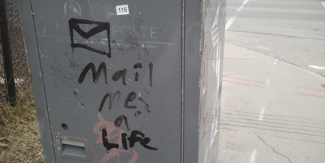 a post box with 'Mail me a Life' graffitied on it