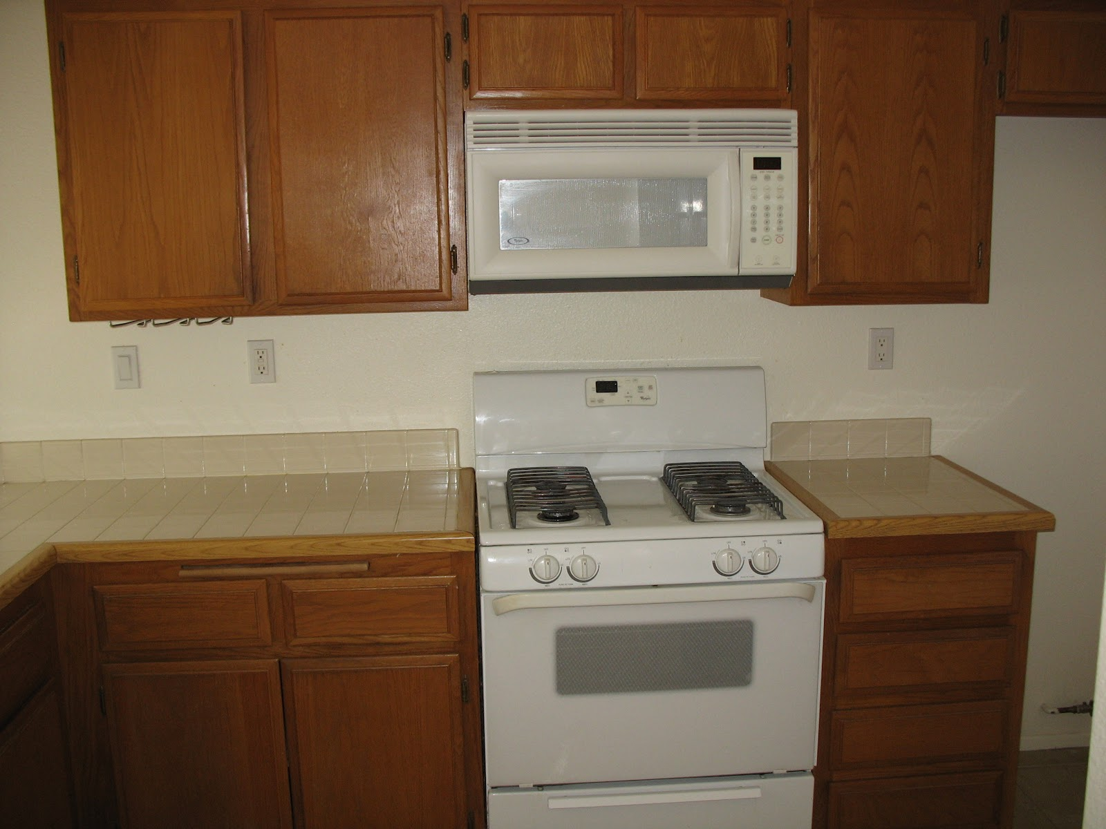 kitchen makeover basic kitchen cabinets Wow I didn t remember how it looked until I searched for these pictures It s your basic builder grade kitchen cabinets and tile counter