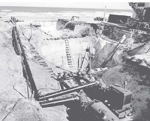An excavation is kept dry despite the close proximity of a large body of water. Two dewatering pumps are visible in the foreground.  A pair of header pipes and numerous well points can be seen surrounding the excavation.