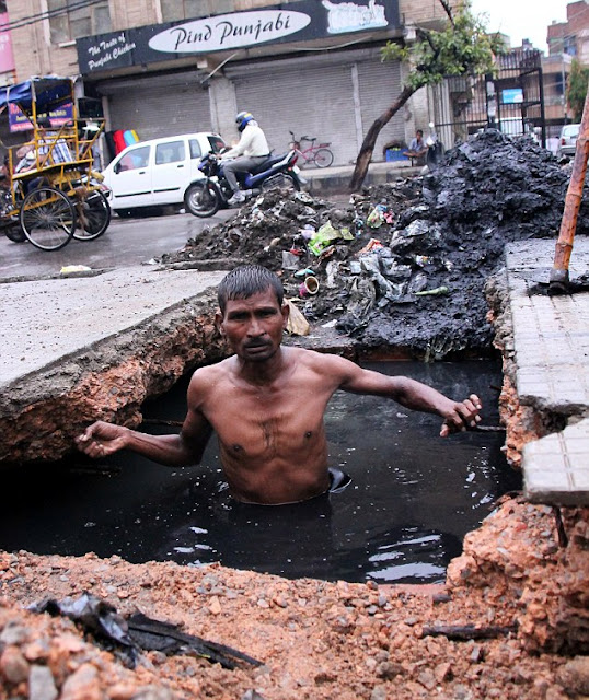 Dirty job: Devi Lal, a sewer diver from Delhi is paid a measly £3.50 a day to unclog the city's filthy drains