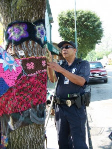 police man helps yarn bomber fix installation