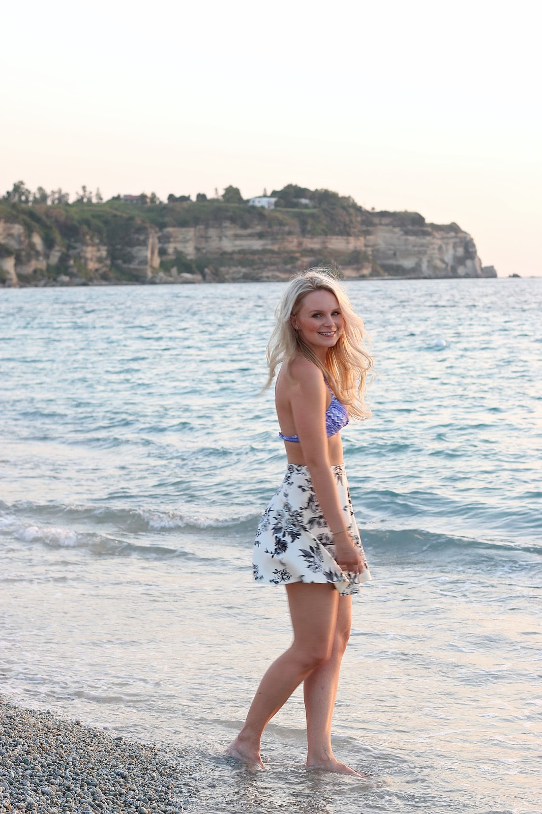 a blonde girl poses in front of beautiful sunset in italy on the beach
