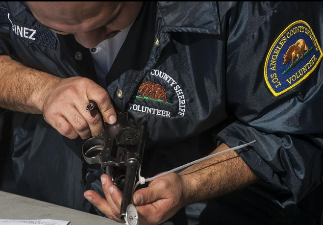 "A Los Angeles County Sheriff's deputy checks a reclaimed pistol during a ""Gifts For Guns"" exchange program"