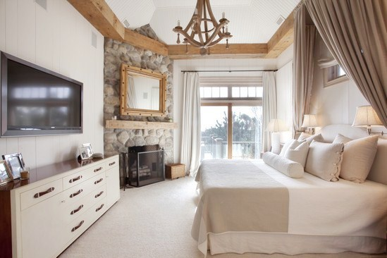 rustic master bedroom with exposed beams, stone fireplace with a large mirror in a wood frame on the mantel, canopy bed, wood chandelier and white drawers with wood handles