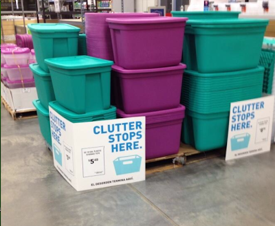 plastic bins being sold, with a sign that says: Clutter stops here.