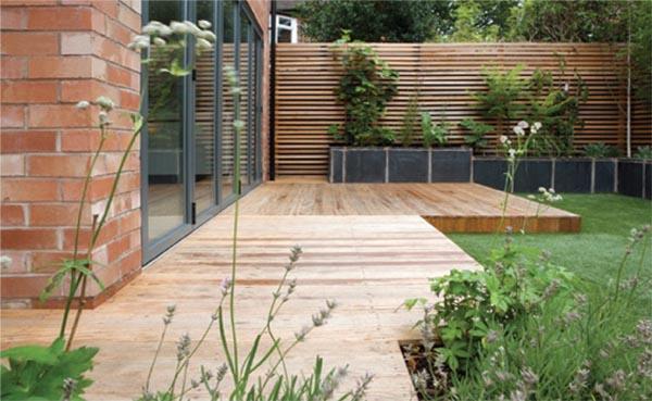 vista general de jardineras con la tarima de madera en el jardin