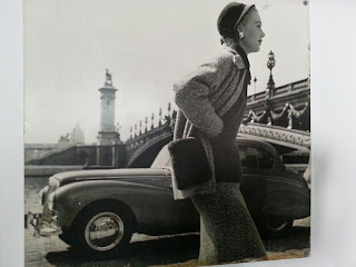 Black and white image of a woman standing in front of an old car and bridge.