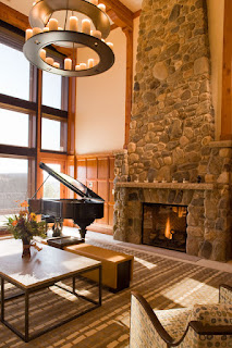 Fantastic View of the Living Room with Stone Rustic Fireplace Mantels and Unique Chandelier above it