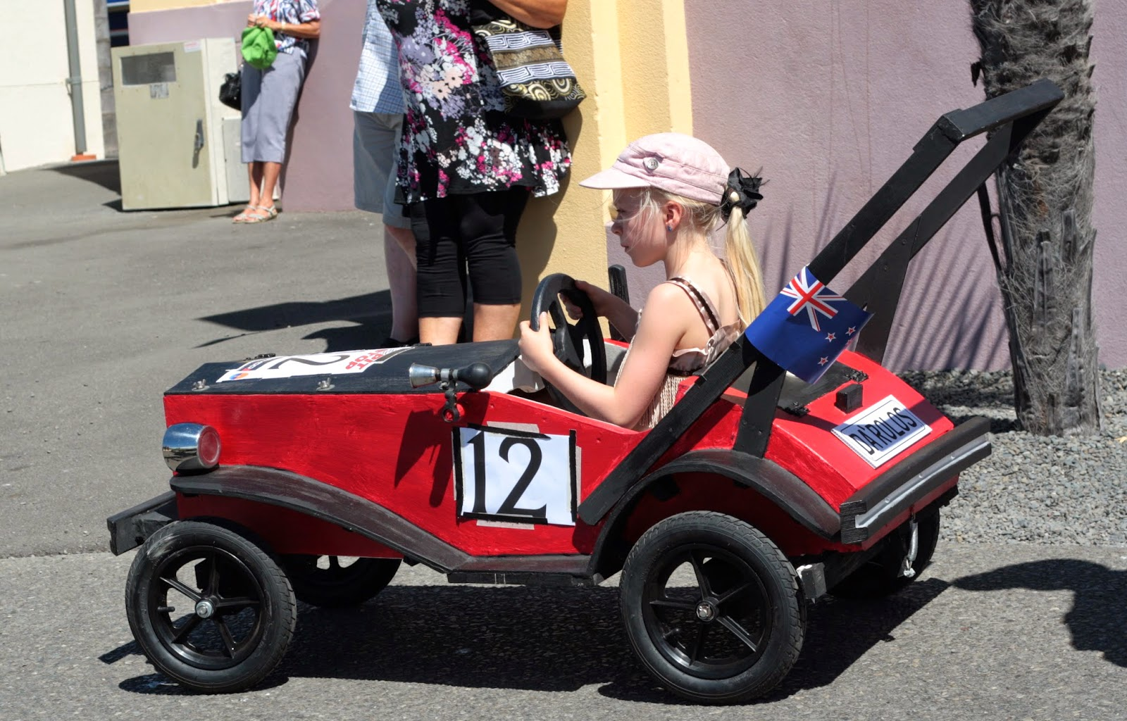 Girl driving a red trolley car.