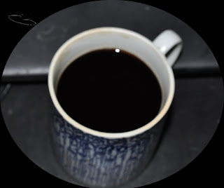 photo of black coffee in a blue and white cup
