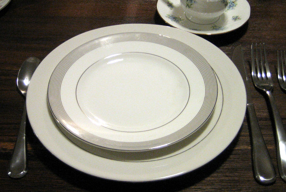 An elegant modern place setting with a small silver stripe.