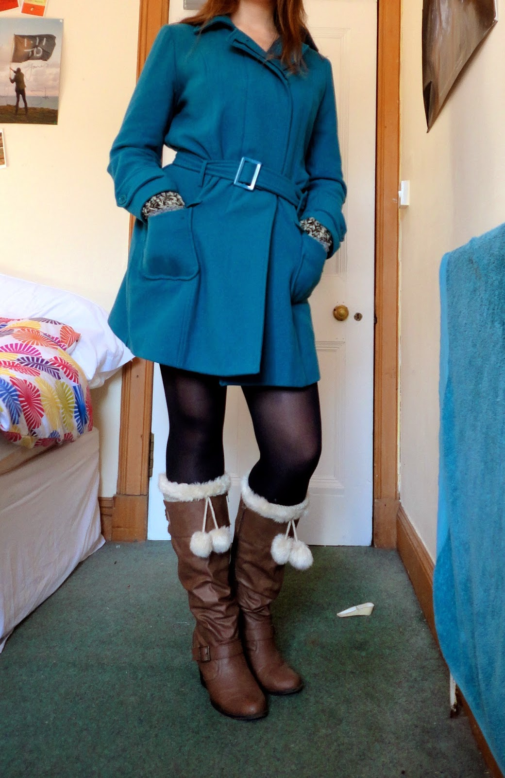outdoor winter outfit of turquoise blue coat and brown leather boots with white fluffy toppers