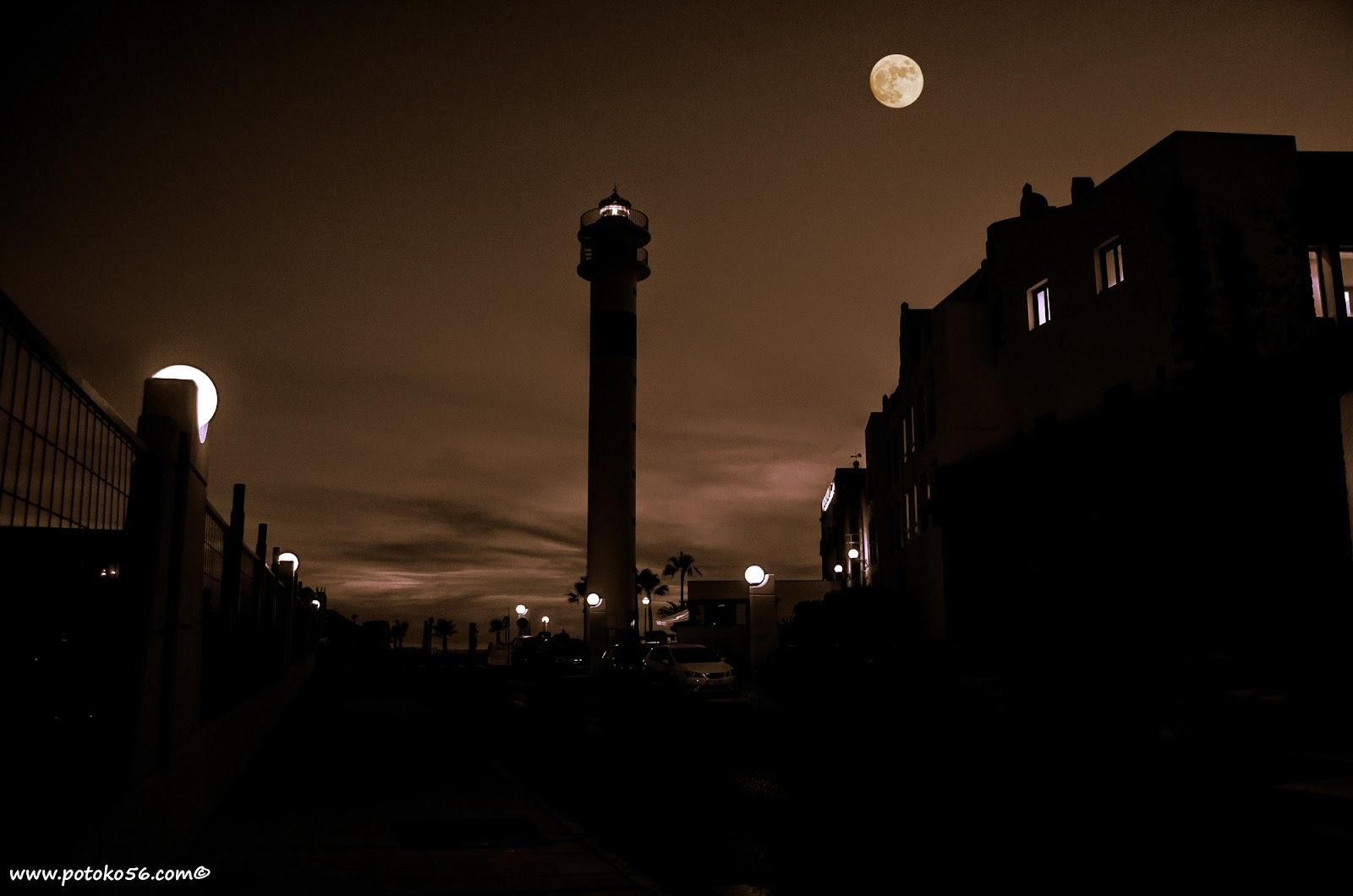 siluetas en la madrugada entrada al muelle de Rota con el Faro