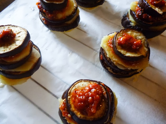 Building the moussaka tower step 3: one more slice of potato and eggplant above and tomato sauce on top