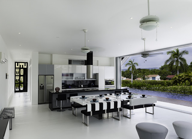 Modern black and white kitchen and dining room by the swimming pool