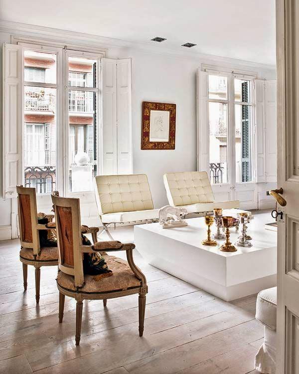 Salon luminoso blanco con butacas vintage sin tapizar