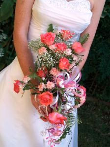 Bride in wedding dress holding boquet of flowers.