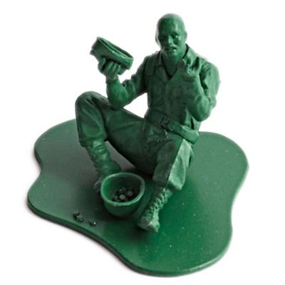 Grøn plastik legetøjs soldat som tigger på gaden