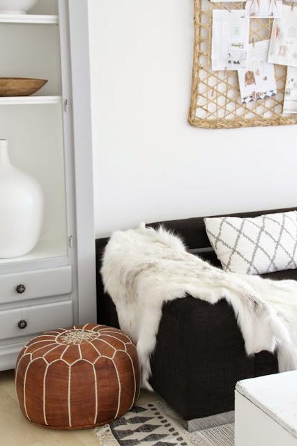 brauner Lederpouf und schwarzes Sofa mit Kissen darüber eine Pinnwand aus Bast