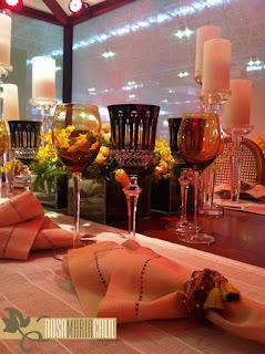 velas, arranjo floral, taças âmbar e pretas, candelabros, guardanapo de linho