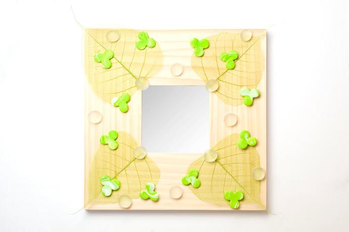 Specchio con foglie, sassi e formine in fimo