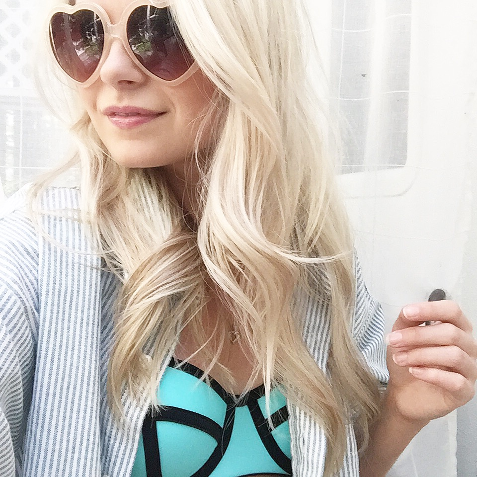 a girl wearing heart sunglasses, striped vintage shirt and blue bikini top