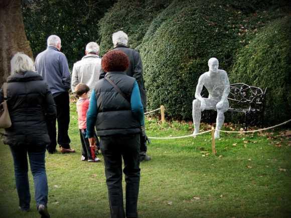 Derek Kinzett esculturas feitas de arames O homem verde sentado no banco e com espectadores