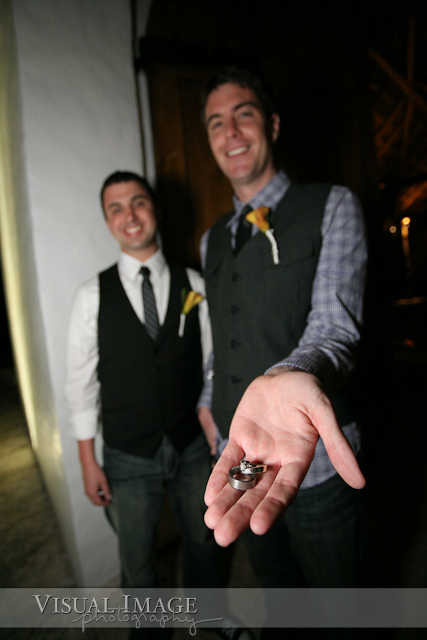 Groom holding wedding rings while standing next to best man
