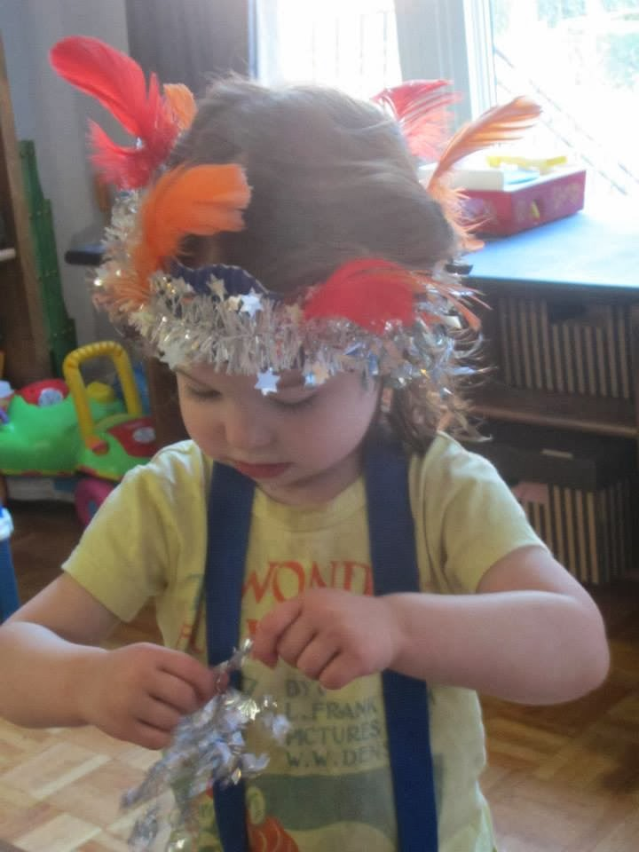 toddler with sparkled feather crown