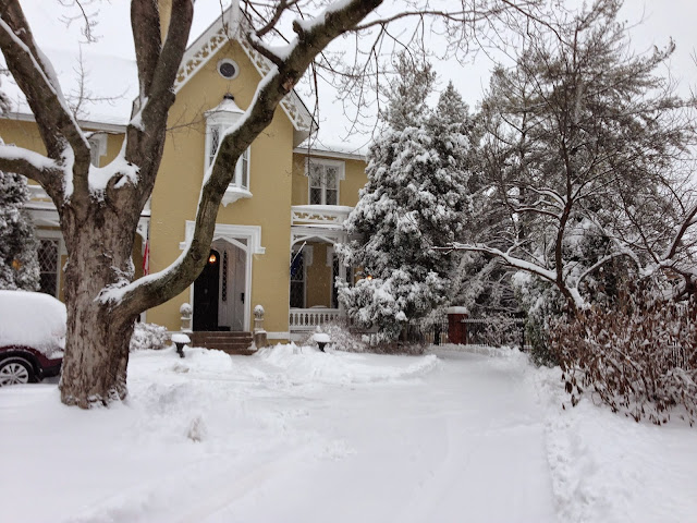 the inn with the main house showing with yellow paint on the house and 6 inches of white snow covering the front yard and the trees and the sign