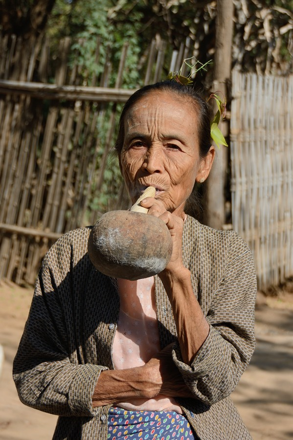 Older woman smoking a large cigar in Min Nan Thu village at Nyaung U near Bagan, Myanmar