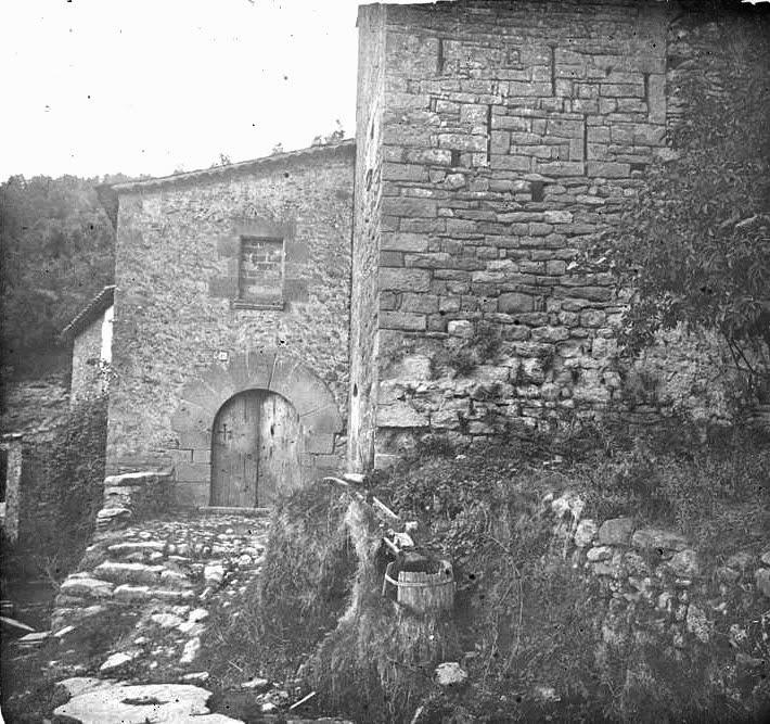 Fotografia de l'any 1922 on apareix la torre del molí i on es poden veure les espitlleres defensives