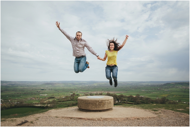 A couple jumping in the air at Glastonbury Tor