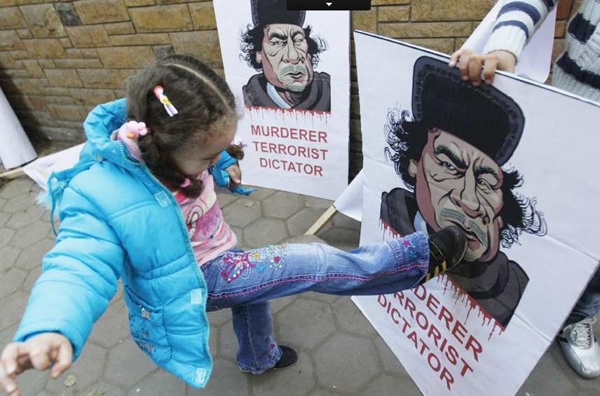 Menina chutando a foto de um ditador