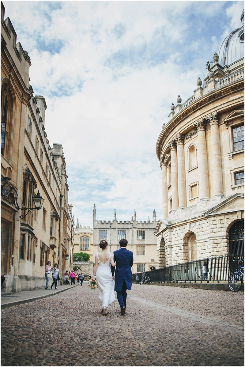 Bride and groom walk past Radcliffe Camera, Oxford