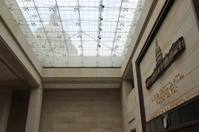 The dome of United States Capitol can be seen through the glass roof of the ground floor of the Visitor Center in Washington DC, USA