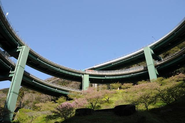 built the Kawazu-Nanadaru Loop Bridge, also known as the Japanese Double loop spiral, in Kawazu, Japan. This double spiral brings cars up and down a full 45 meters while being seemingly suspended in a valley between two mountainsides. The spirals measure 80m in diameter and the whole ramp section is 1.1km long.