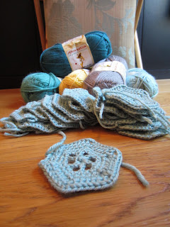a stack of crochet hexagons piled in front of yarn and knitting bag