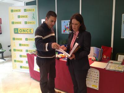 La imagen muestra al maestro del Equipo enseñándole a la alcaldesa una cartilla braille.