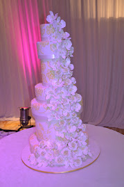 7 tier stacked with sugar roses and phaelopsis orchids with brush embroidery piping .