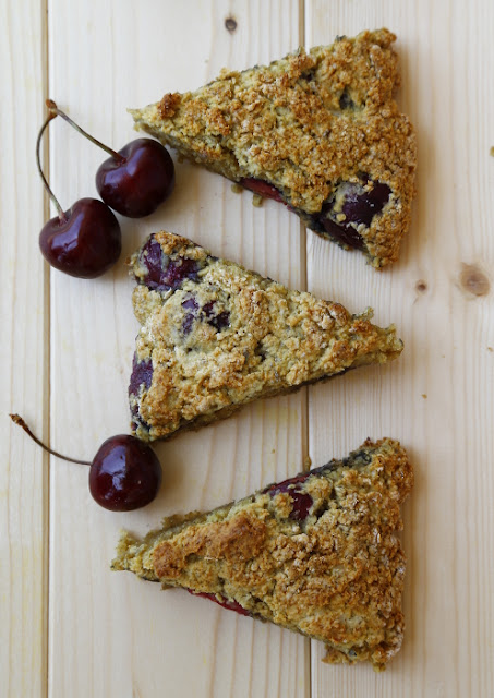 Slices of black cherry scones and cherries on a wooden background