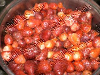 نزع الأوراق الخضراء من الفراولة تمهيدا لحفظ الفراولة فى الفريزر