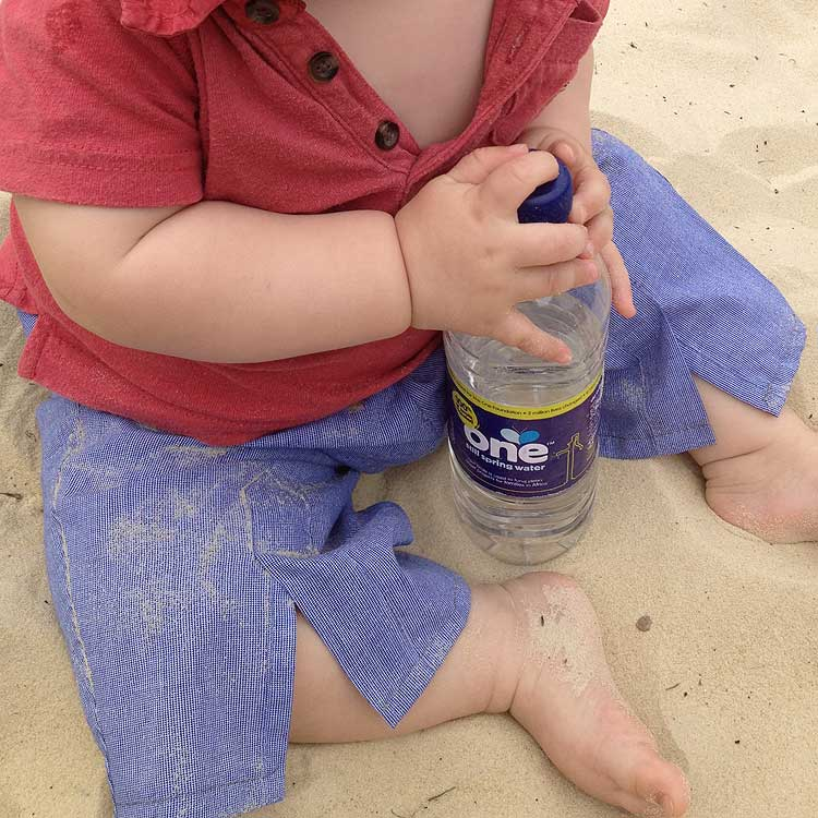 sitting down wearing trousers with bottle