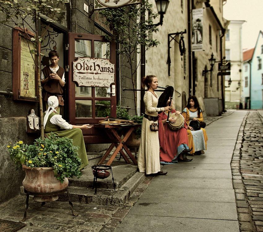 Grupo de figurantes vestidos com trajes da Idade Média, uns tocando outros conversando. Tonalidade da imagem a simular uma foto antiga