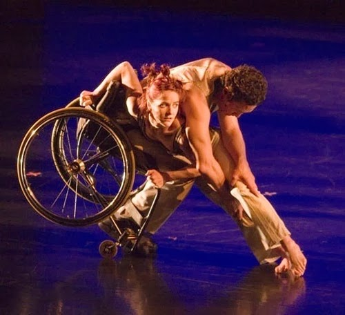 Woman in a wheelchair dancing with man