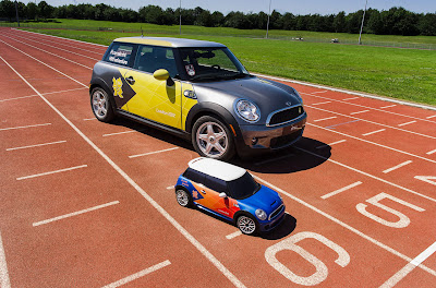 "Dubbed ""Mini MINI,"" these three electric R/C Cooper hatchbacks are rendered in about 1/4-scale – necessary to ensure adequate payload capacity for up to eight kilos (nearly 18 pounds). That's enough carrying capacity to lug around a hammer, a discus, a shot or a pair of javelins. The cars' large scale also helps them pack the larger battery arrays that Mini says are necessary to run them for 35 minutes (before being down for 80 minutes of charge time). The models are painted blue with orange Olympic livery and white roofs, and they even have working headlights."